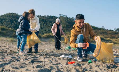 Giovane che raccoglie spazzatura con un gruppo di volontari sulla spiaggia