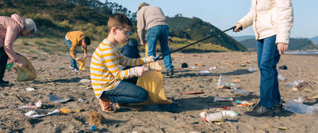Grandmother and grandson with group of volunteers picking up trash on the beach Stock Photo