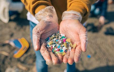 Détail des mains montrant des microplastiques sur la plage
