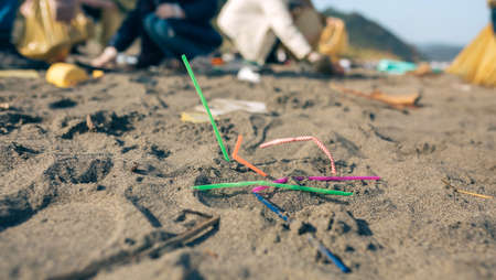 Straws thrown on the beach with group of volunteers working in the background. Selective focus in straws in foreground