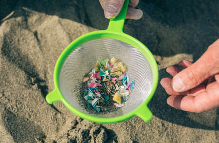 Detail of hands holding colander with microplastics on the beach