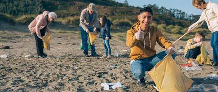 Jeune homme ramassant des ordures avec un groupe de bénévoles sur la plage