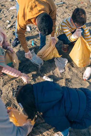 Top viewo of group of volunteers picking up trash on the beach