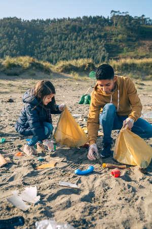 Des jeunes bénévoles ramassent des ordures sur la plage Banque d'images