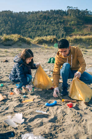 Young volunteers picking up trash on the beach Stock Photo
