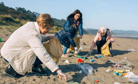 Group of female volunteers picking up trash on the beach. Selective focus on woman in foreground Reklamní fotografie
