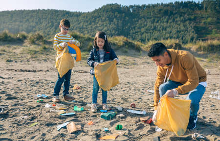 Group of young volunteers picking up trash on the beach 스톡 콘텐츠