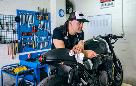 Mechanic posing with a customized motorcycle in his workshop