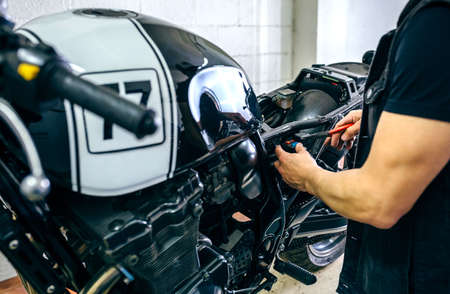 Mechanic repairing customized motorcycle by changing a fuse in the workshop Stock Photo