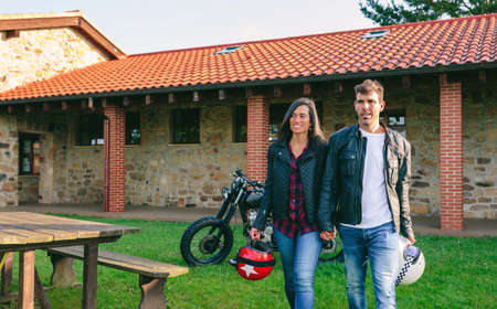 Young couple walking holding hands outdoors with custom motorcycle in the background