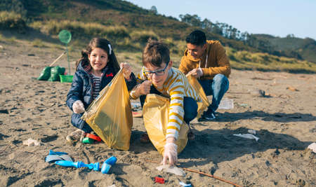 Group of young volunteers picking up trash on the beach Foto de archivo