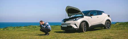 Young man desperate because his car has broken down, near the coast