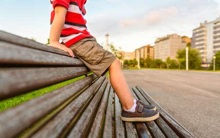 Nahaufnahme von Jungenbeinen mit kurzen Hosen, die oben auf hölzernem Bankpark sitzen, der an einem gelangweilten Sommertag entspannt