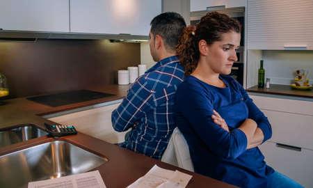 Giovani coppie arrabbiate che si siedono schiena contro schiena dopo una dura lite dai loro molti debiti a casa. Concetto di problemi familiari finanziari.
