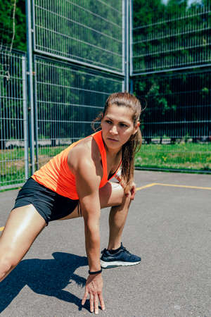 Young sportswoman doing leg stretches on a sports court