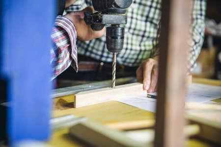 Unrecognizable senior couple drilling a wooden batten in their workshop