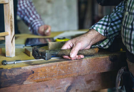 Detail of carpenters hand holding a hammer leaning on the workbench Stock fotó