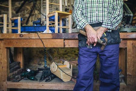 Unrecognizable senior carpenter posing with a hammer Stockfoto