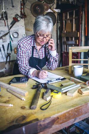 Senior female carpenter talking on the phone in his workshop