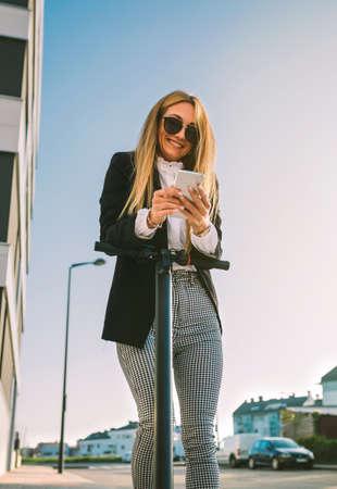 La empresaria recostada sobre su scooter eléctrico mirando el móvil en la calle Foto de archivo
