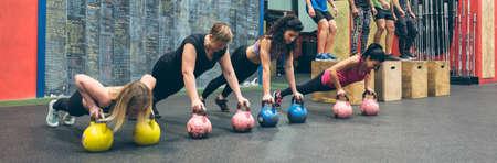 Sportswomen doing push-ups with kettlebells and sportsmen doing box jumps Stock Photo