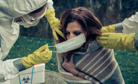 Man and woman in bacteriological protective putting a mask on sick woman Stockfoto