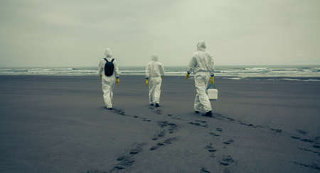 Unrecognizable people with bacteriological protection suits walking on the sand of the beach Stockfoto