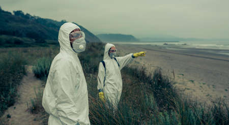 Man and woman in bacteriological protective suits watching and pointing to the sea
