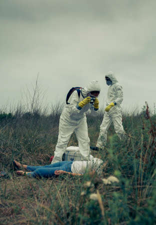Woman in bacteriological protective suit taking a photo of a corpse, and her partner in the background examining the area