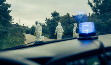 View from emergency car of people with bacteriological protection suits walking on a road looking for evidence Stockfoto