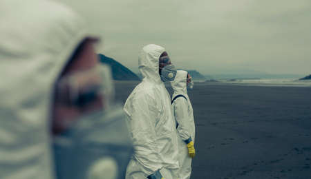People with bacteriological protection suits on the beach looking at the sea Stockfoto