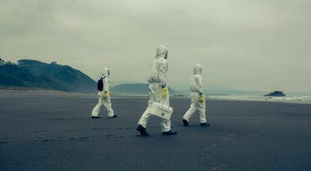 Personnes méconnaissables avec des combinaisons de protection bactériologique marchant sur le sable de la plage