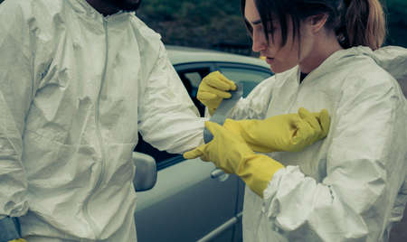 Woman taping bacteriological protective suit gloves to a man outdoors Stockfoto