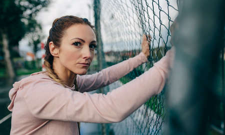 Young sporty girl with challenging look resting on sports court fence Foto de archivo