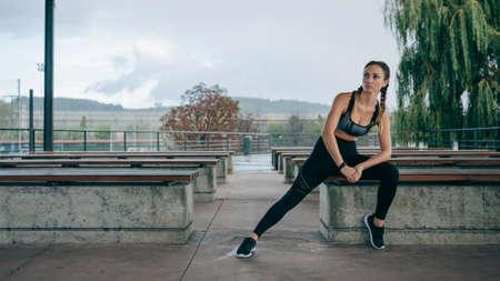Junge Sportlerin posiert draußen auf einer Bank sitzend