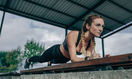 Young sportswoman doing plank on a bench outdoors on a rainy day