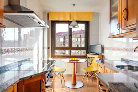 Interior of kitchen on two fronts with dining area next to the window Stok Fotoğraf