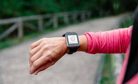 Detail of athlete woman arm using smartwatch with sport app