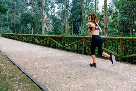 Unrecognizable athlete woman running through a park Banco de Imagens