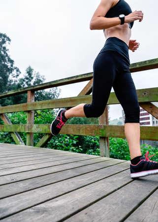 Unrecognizable athlete woman running through an urban park Stock Photo