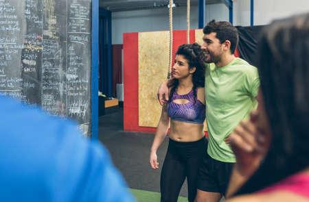 Par de atletas mirando resultados en la pizarra del gimnasio