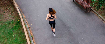 Top view of female athlete backwards running on a road Stockfoto