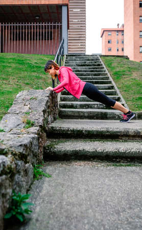 Young female athlete doing push-ups supported on a wall outdoors