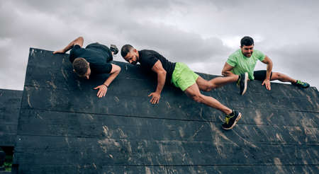 Group of participants in an obstacle course climbing an inverted wall 版權商用圖片