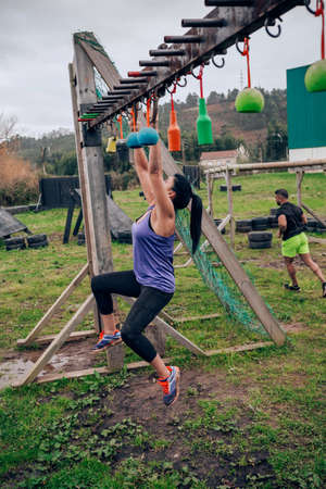 Female participant in an obstacle course doing suspension ring exercises
