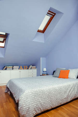 Bedroom in an attic with double bed and chest of drawers with books Stock fotó