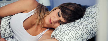 Pretty young woman sleeping peacefully in bed Stock fotó