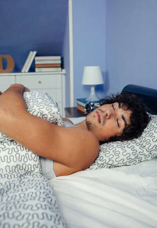 Young man deep asleep in bed at home