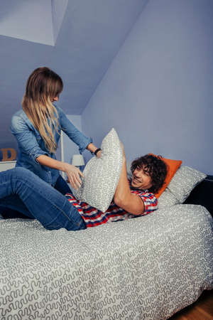 Top view of young couple in confinement for a virus making a pillow fight on the bed