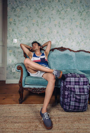 Young man with suitcase waiting sitting on a sofa to return to his country Foto de archivo